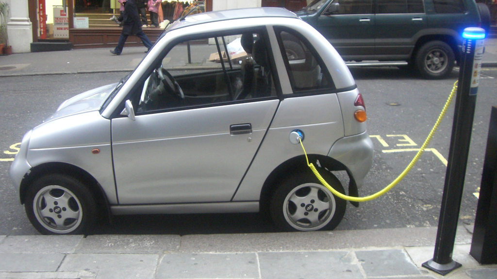 An electric car is pictured plugged into its charging station on the street