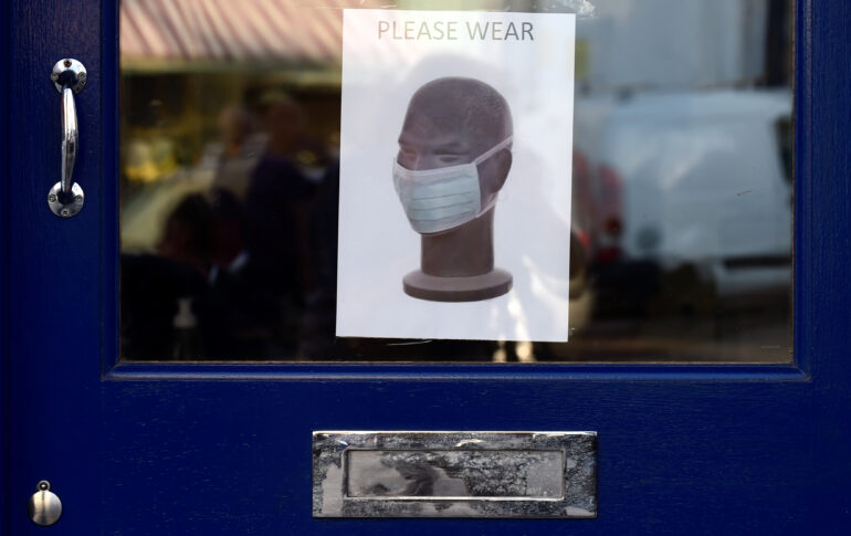 A poster is seen on a door requiring to wear a mask during the outbreak of the coronavirus disease (COVID-19) in Tenby, Wales, Britain September 14, 2020. REUTERS/Rebecca Naden
