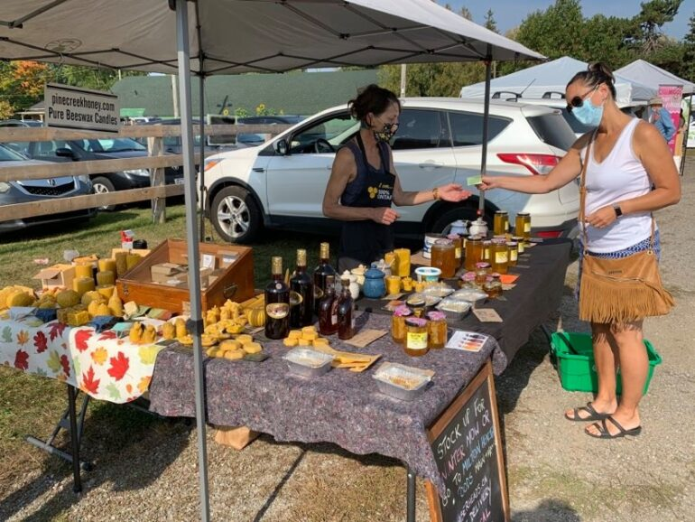 Susan Frame (left) owner of Pinecreek Honey with customer during Milton's Farmers Market.