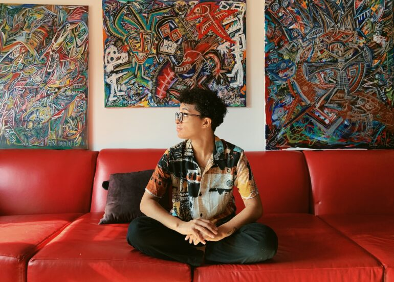 Miyakah Lindo in front of some of their abstract pieces of art. Photo Cred. Alexis Silvera