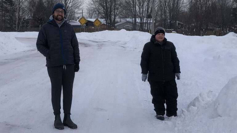 Jonathan Mogg and his nine-year-old son Alex walking down the street in Sault Ste. Marie Ont.