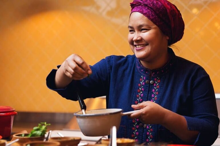 Executive Chef Nuit Regular smiles as she puts the finishing touches on a dish at her downtown Toronto restaurant, PAI. Along with her husband, Jeff Regular, she owns four restaurants and is preparing for an active summer with CaféTO. Photo credits: Chef Nuit Regular.