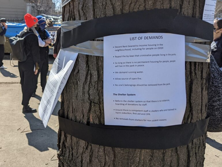 A list of demands taped to a tree near Alexandra Park's homeless encampment. Residents and advocates are asking the city to improve park spaces and the shelter system.