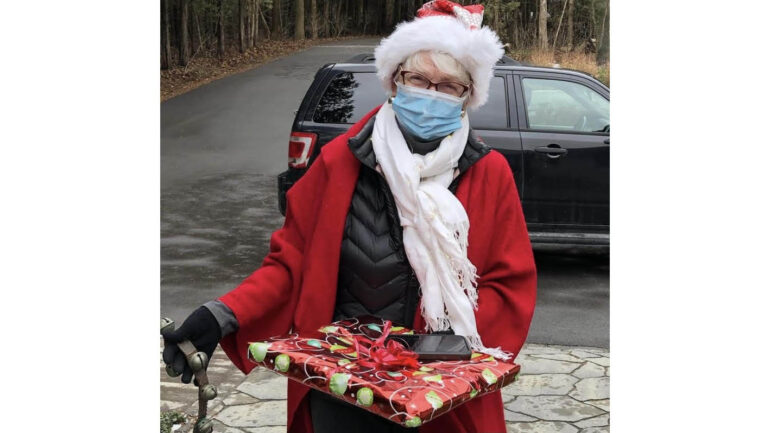 Pamela Carter dressed as Santa Claus delivering one of the paintings to a woman who bought a piece as a Christmas present for her husband. The earnings became a part of Pamela's fundraiser.