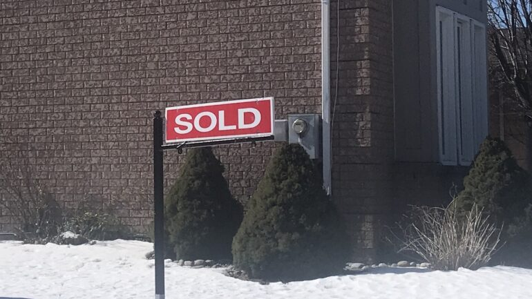 "A ""sold"" real estate sign outside of a home."