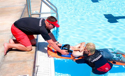 Two lifeguards practice a drill to remove a victim from shallow water using a spinal board. The Lifesaving Society said lowering the age required to certify as a lifeguard was partly due to widespread staff shortages across the country. Photo Credits: Red Cross.