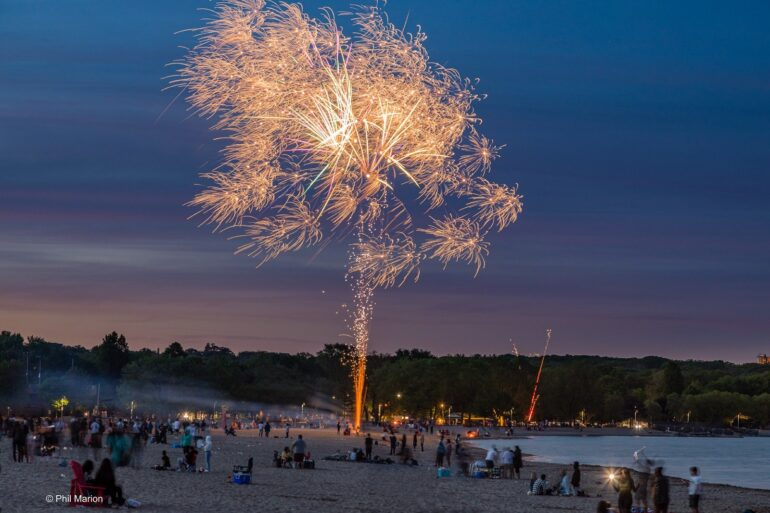 Fireworks on a beach with crowds of people surrounding