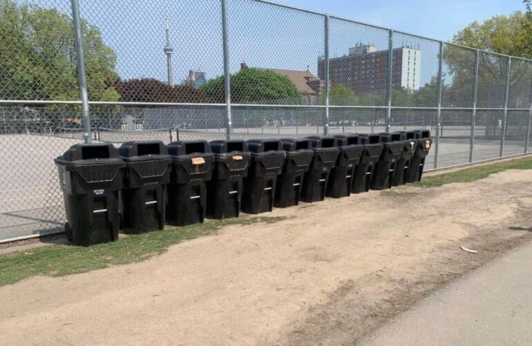 Garbage bins lined up along a park fence
