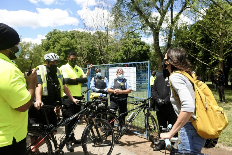 Elizabeth Gallou, a Toronto woman and advocate of Encampment Support Network, confronts a group of police officers and security guards at Trinity Bellwoods Park.