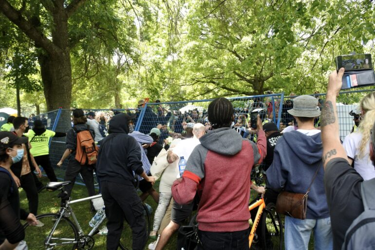 The crowd of supporters and protestors topples down the fencing surrounding the encampments after about 25 people were evicted from Trinity Bellwoods Park.
