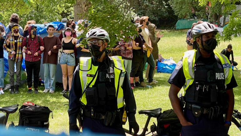 Protesters link arms to protect a tent in Trinity-Bellwoods Park in west Toronto as city crews move in to dismantle them. About 25 homeless people who were living in the park were evicted.