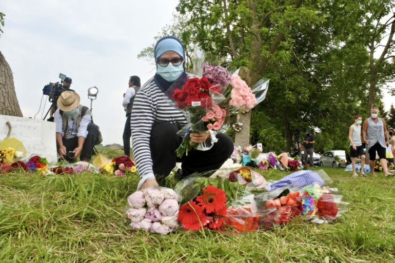 Zina Atta arranges bouquets if flowers at a growing memorial where London of five were run over in a suspected hate crime on Hyde Park and South Carriage Roads.