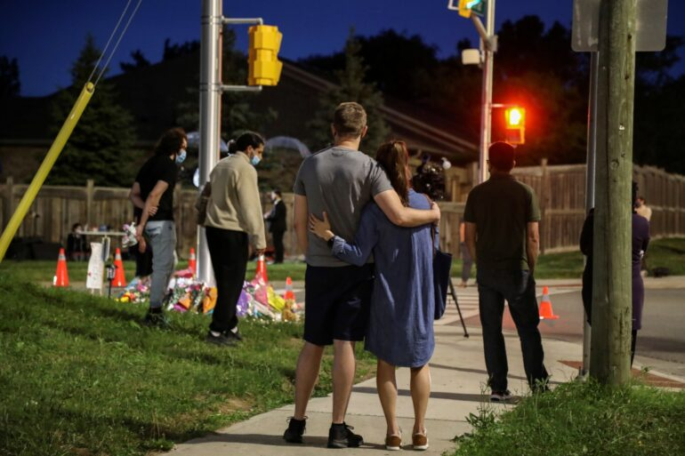 People at a makeshift memorial at the fatal crime scene June 7 where a man driving a pickup truck jumped the curb and ran over a Muslim family in what police say was a deliberately targeted anti-Islamic hate crime in London, Ont.