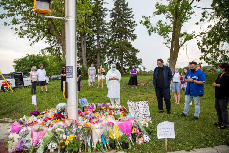 People are seen at a makeshift memorial at the fatal crime scene where a man driving a pickup truck jumped the curb and ran over a Muslim family in what police say was a deliberately targeted anti-Islamic hate crime, in London, Ontario, Canada June 8, 2021.