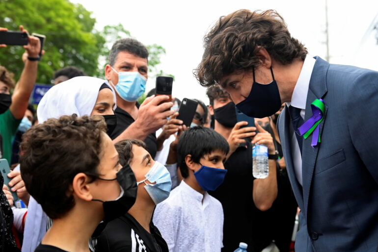 Prime Minister Justin Trudeau interacts with youths at a vigil June 8 outside the London Muslim Mosque organized after four members of a Canadian Muslim family were killed in what police describe as a hate-motivated attack in London, Ont.