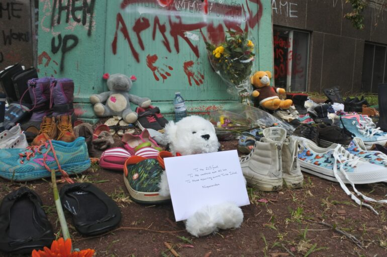 A teddy bear holds a letter to the 215 children found buried on the grounds of the Kamloops Residential School. The area around the Gould Street statue has become a memorial site.