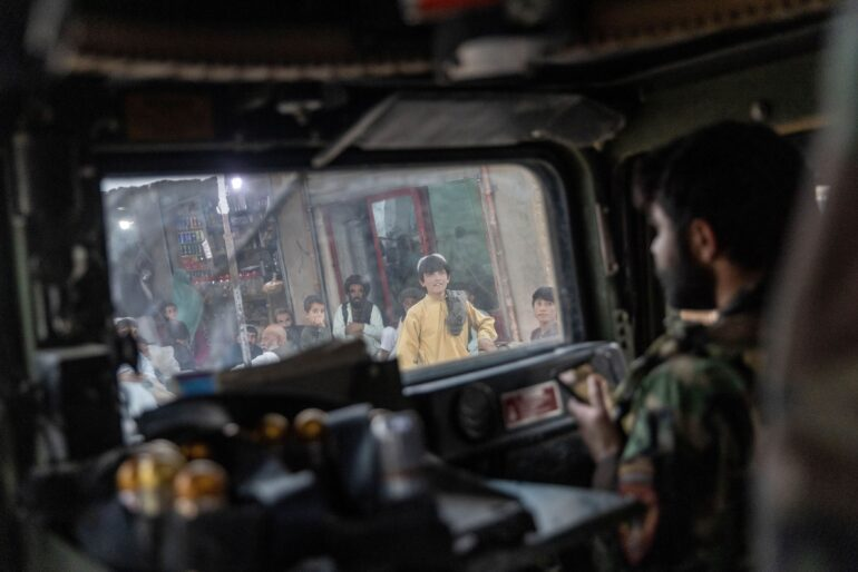 People watch as the convoy of Afghan Special Forces passes through a market during a combat mission against Taliban, in Kandahar province, Afghanistan, July 12.