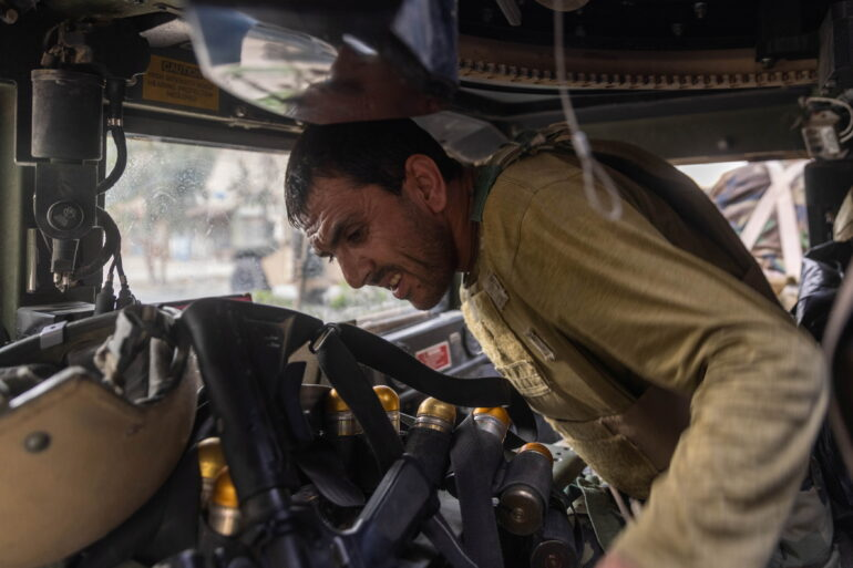 Members of Afghan Special Forces travelling in a humvee destroyed during heavy clashes with Taliban take cover during the rescue mission of a policeman besieged at a check post, in Kandahar province, Afghanistan, July 13.