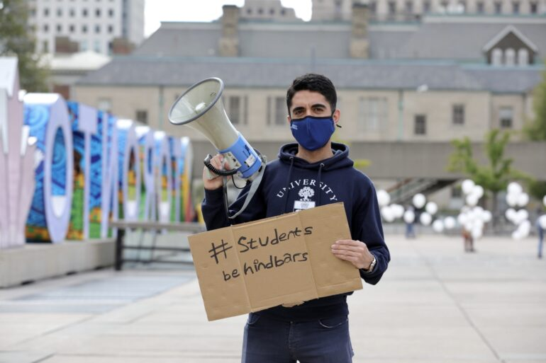 A Cadet from the protest is carrying a banner to raise awareness and explaining the aim of the protest with megaphone in Nathan Philips Square on Sept. 10, 2021.