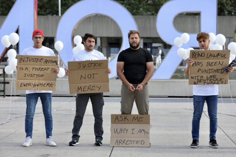 Four students from the right to the left are shouting slogans for their arrested friends and carrying banners for the explanation in Nathan Philips Square on Sept. 10, 2021.