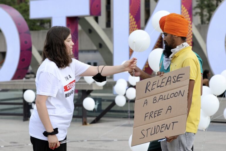 A visitor on the right behind side released a baloon to represent a jailed cadet student. other visiter carries a banner. On the left side, a cadet student helps them.